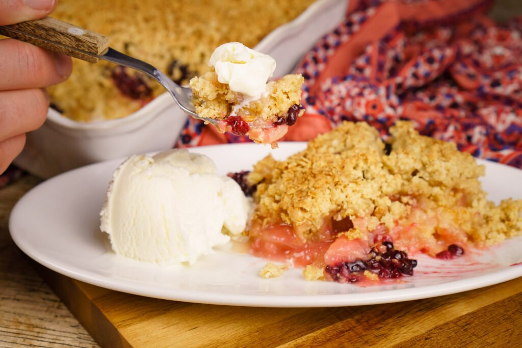 Apple and Blackberry Crumble served with vanilla ice cream on a white plate and some being scooped up with a spoon to eat