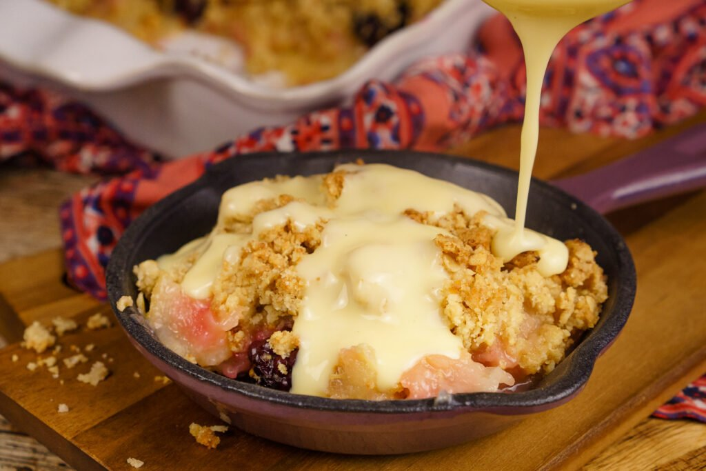 Pouring custard on top of apple and blackberry crumble served in a mini cast pan