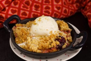 Apple and Blackberry Crumble served in a mini cast iron pan with melted vanilla ice cream on top