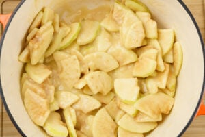 Sliced cooking apples coated in a roux mixture in a pot
