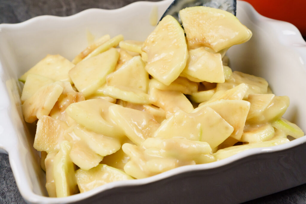 Placing the coated slices of coated cooking apples into an oven proof dish