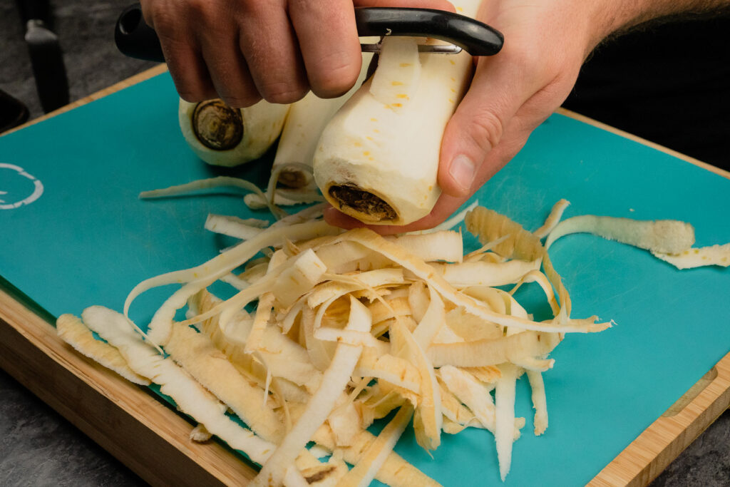 Peeling parsnips with a black peeler by hand on a blue chopping board