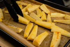 Turning the honey parsnips over with black tongs