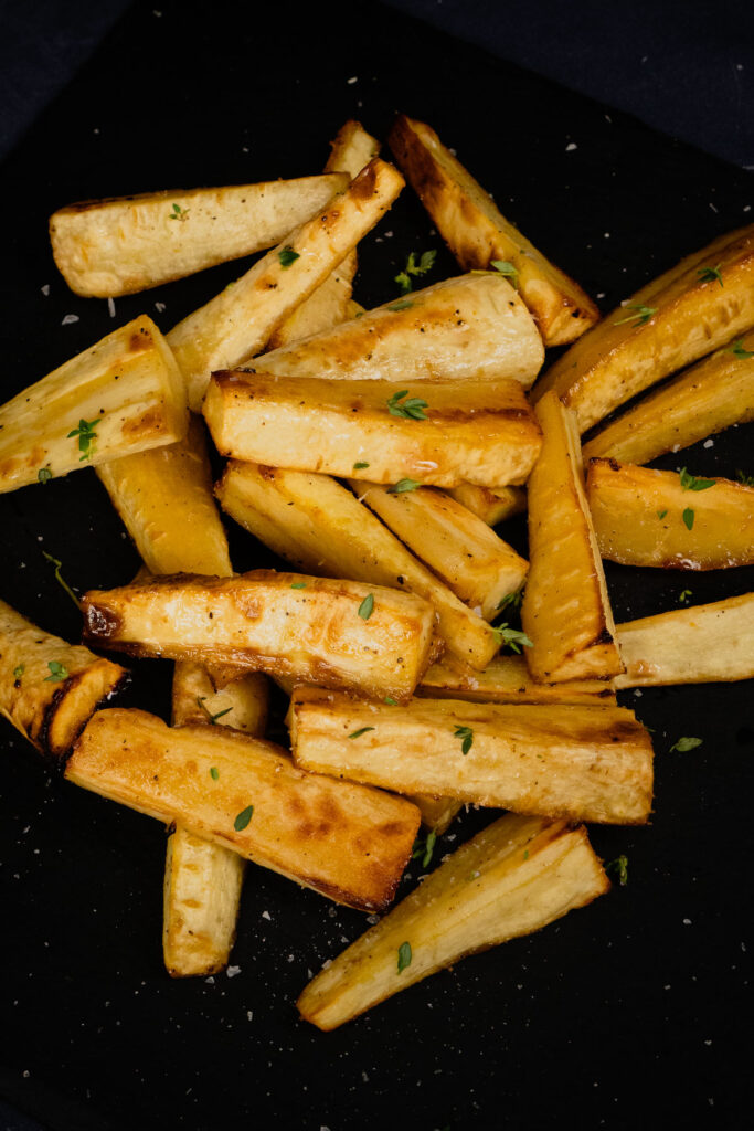 Long pin image of our Honey Roast Parsnips with fresh thyme sprinkled over the top served on a black slate plate