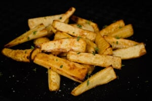 Close up image of our Honey Roast Parsnips with fresh thyme sprinkled over the top served on a black slate plate