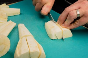 Chopping the parsnips into slices with a silver knife by hand