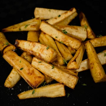 Honey Roast Parsnips with fresh thyme sprinkled over the top served on a black slate plate