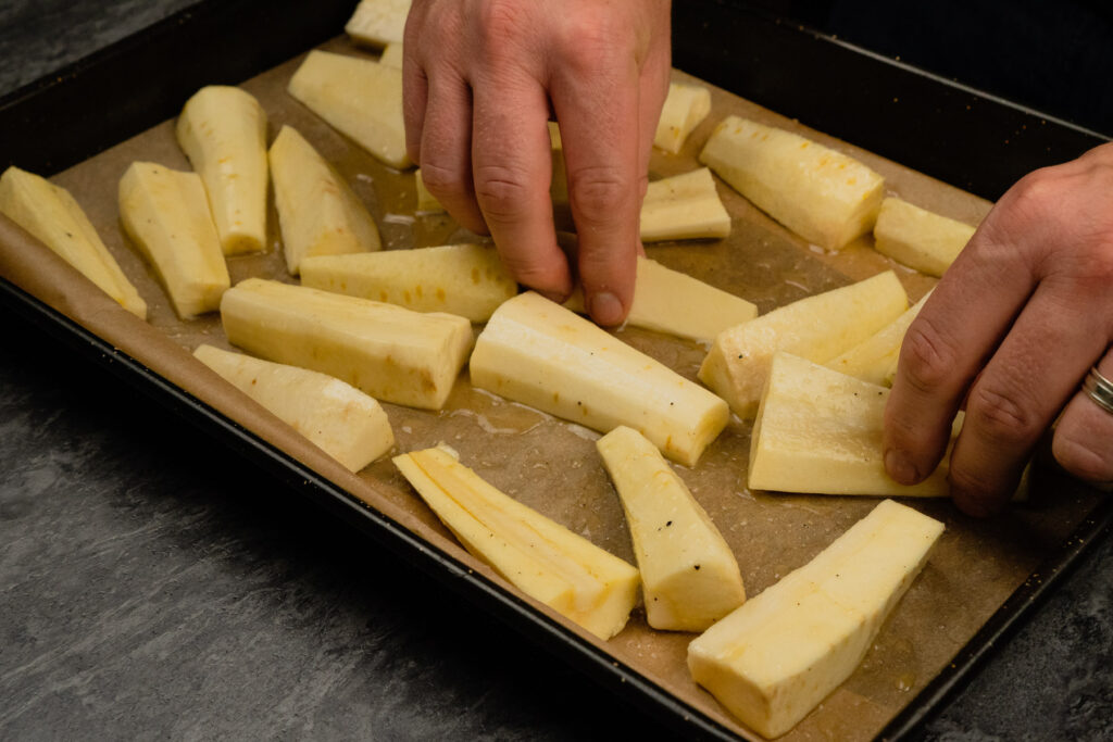 Placing down the honey coated parsnips onto a baking tray by hand lined with brown parchment paper