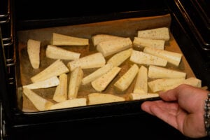 Placing a baking tray with honey coated parsnips into the oven by hand